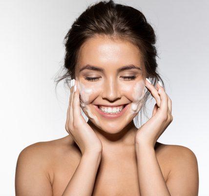 Codzienna pielęgnacja twarzy - uśmiechnięta kobieta nakładająca krem na twarz.